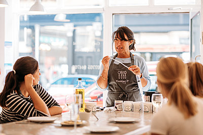 host explaining ingredients in a cookery workshop
