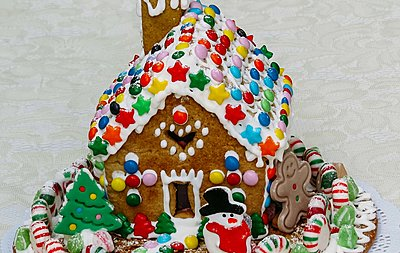 colourful gingerbread house surrounded by sweets