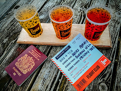 three pints of cider on a table with a passport