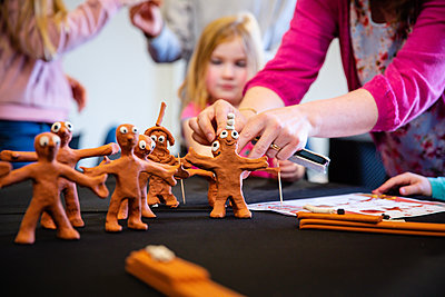 child creating a clay model of morph