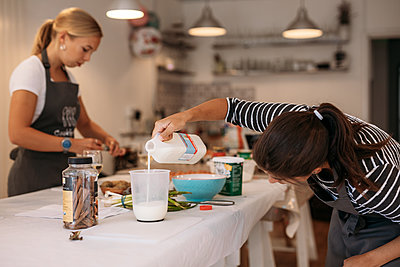 person measuring milk in a cookery class