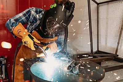 person welding scrap metal