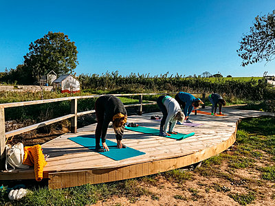 people doing yoga outdoors on decking