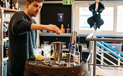 man making a cocktail adding gin to a shaker