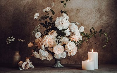 big bouquet of flowers next to candles