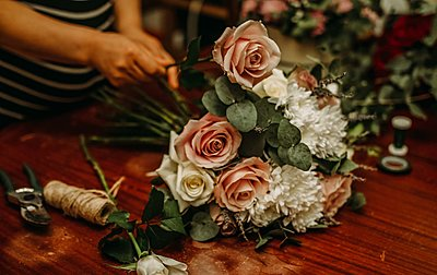 person making a large posy of pink and white flowers