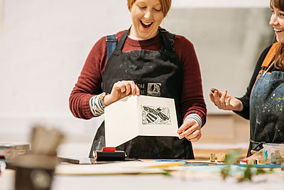 person in an apron looking at a monoprint image