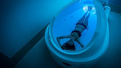 person floating in a private flotation pod