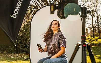 woman taking a selfie with professional photography equipment