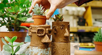 two ceramic pots with faces and plants for hair