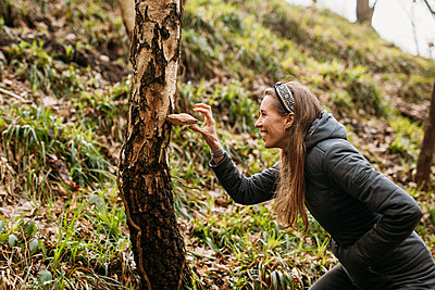 woman looking at a mushroom growing from a tree
