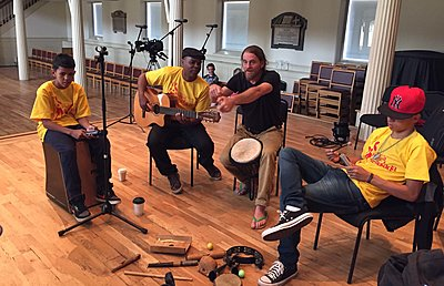 instructor leading a group sitting in a circle playing musical instruments