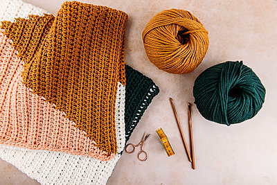 cosy blanket, wool and knitting needles on a table