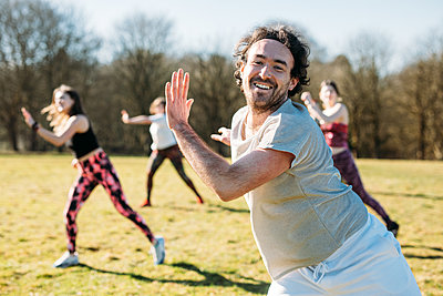 smiling man leading a group in an outdoor dance fitness class