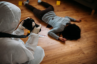 forensic scientist taking a picture of person lying on the floor