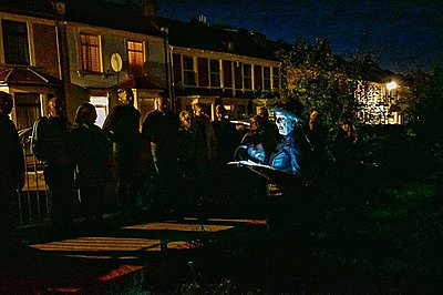 tour guide lit by a torch reading to a group at night
