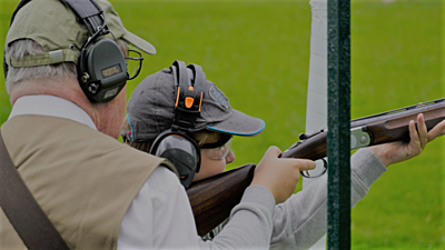 person clay pigeon shooting with instructor watching