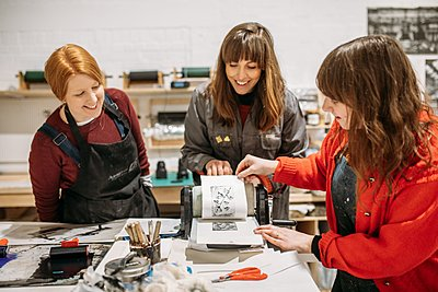 group looking at a monoprint created in a workshop