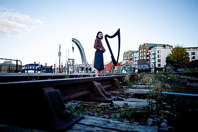 woman stood next to a harp on an old train track