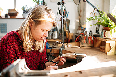 woman metalworking to make a silver ring in a workshop