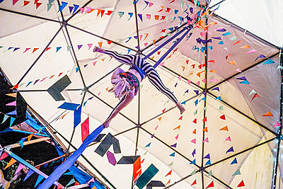 aerial circus artist performing with silks in colourful tent
