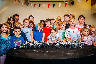 group of children standing behind clay models of shaun the sheep