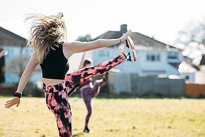 person kicking leg up in a dance class