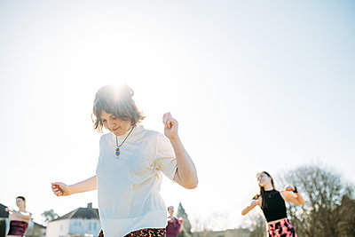 group taking part in a dance workout outside in the sun