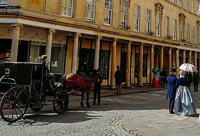 horse-drawn carriage and people in a street in bath
