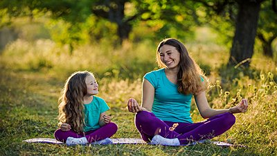 mother and daughter sitting outside meditating together