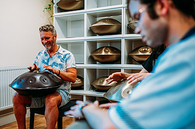 Guests sit down playing handpan drums