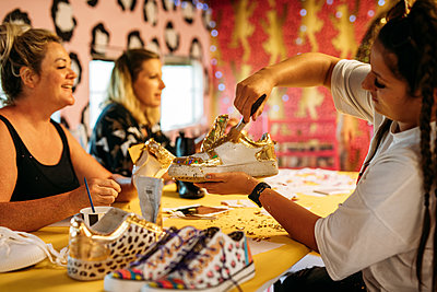 Guest adds gold motifs and glitter to their white trainers in a workshop