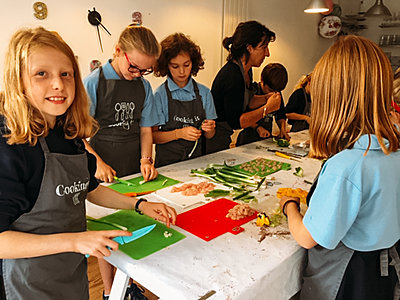 Children wearing Cooking It aprons prepare vegetables in a cooking workshop