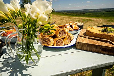 Picnic spread of sausage rolls, scotch eggs, vegetables and pie