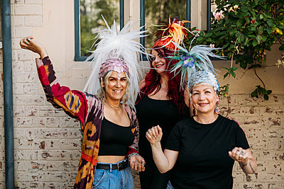 Guest pose with their feathered, bright coloured showgirl hats