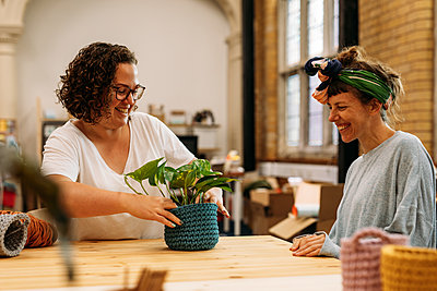 Host and guest admire blue knitted plant basket