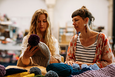 Host and guest study a grey knitted bobble hat