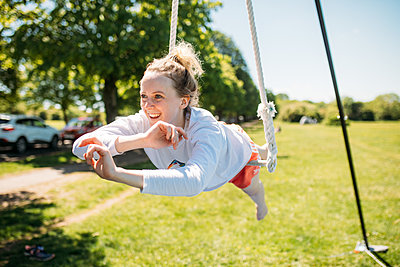 Smiling guest practises an aerial move where they balance on a rope swing outside