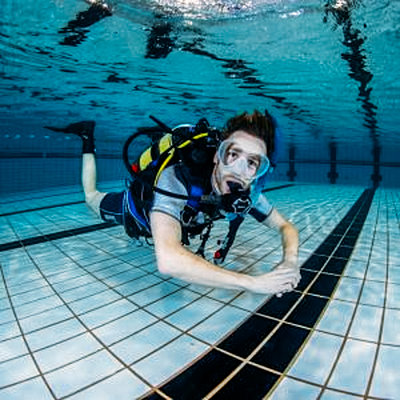 A male scuba diver in full gear poses at the camera underwater