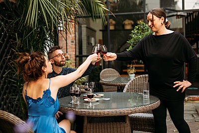 Guests and the host raise their red wine glasses and cheers at the table