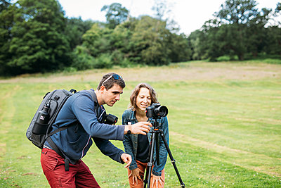 A photographer guides their student on how to take a photo outdoors