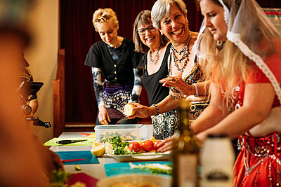 Women gather together around a food prep table and laugh