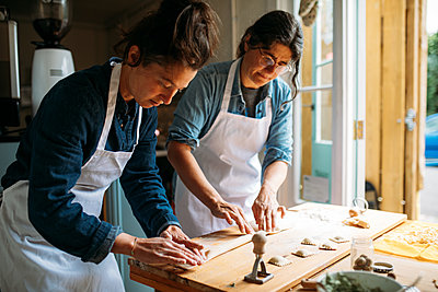 Women carefully begin to shape their ravioli pasta