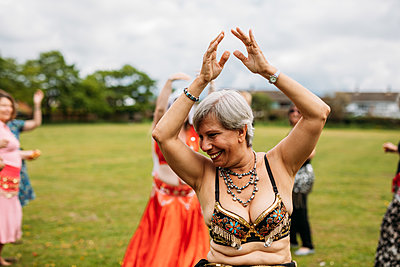 A happy woman raises her arms up to belly dance outside