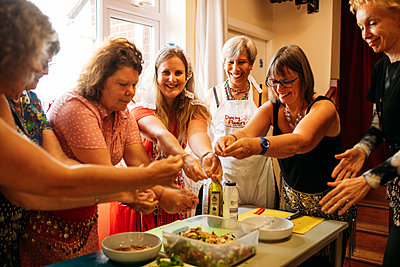 Women preparing food at a table put their hands together and smile