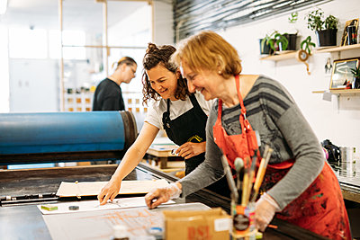 A host and guest in a print workshop stand over a table and look at a design