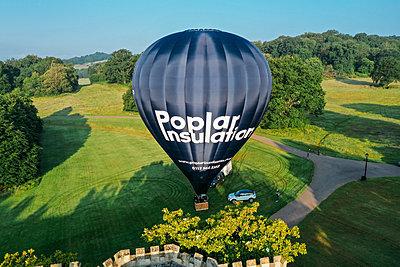 Blue hot air ballon prepares for flight from Ashton Court's green estate
