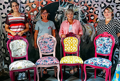 Four happy guests stand behind their brightly coloured upholstered chairs