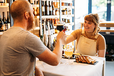 Two happy people seated in a shop raise their beer glasses and cheers
