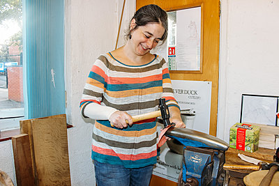 The host smiles as she uses a hammer in her workshop